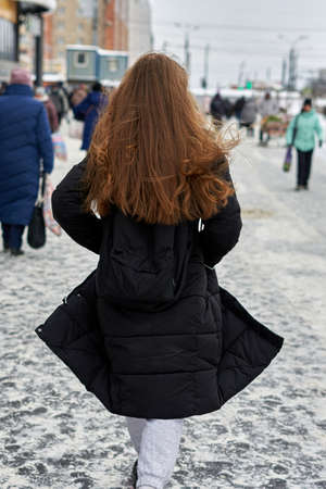 A girl with loose long hair in a black coat t goes on a winter street