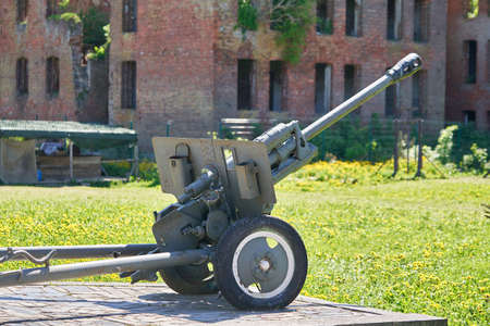 A cannon from the Second World War against the background of a destroyed red brick building