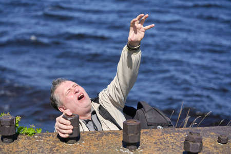 Freak clings his hands to the edge of the cliff above the water Standard-Bild