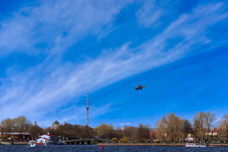The helicopter takes off against the background of clouds and blue sky Standard-Bild