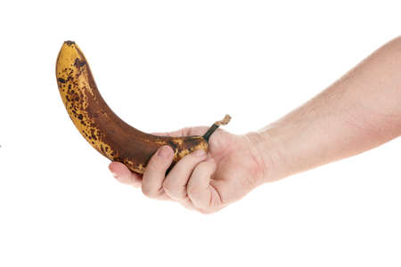 Hand holds a ripe banana on a white background, template for designers Standard-Bild
