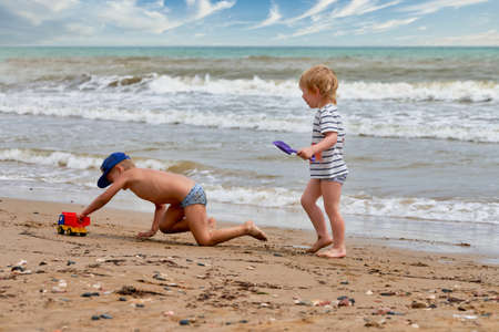 Two little boys are playing on the seashore