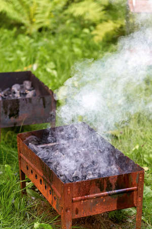 Firing up an old rusty metal barbecue grill, smoke and fire Standard-Bild