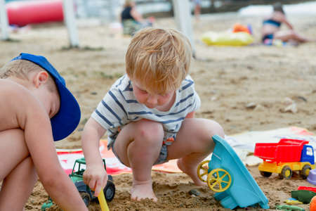 Two children play in the sand with plastic toys