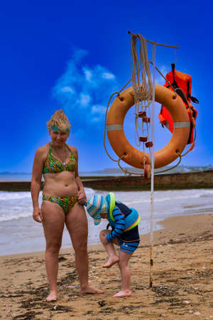 A woman and a child next to a rescue stand at the sea