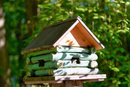 Wooden birdhouse in the form of a house on a stump in the park Standard-Bild