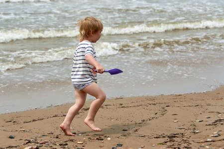 A little boy runs along the sandy beach along the seashore Standard-Bild