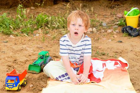 A little boy sits on a towel on a sandy beach among toys Standard-Bild