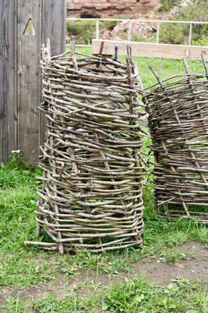 This high handmade basket is woven of tree branches. Old rustic utensils