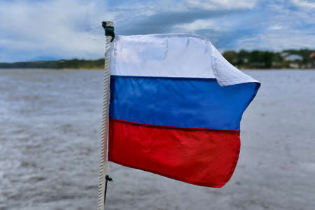 The flag of Russia flies in the wind against the background of the seascape. Three colored flag on a background of water