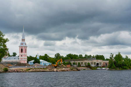 River landscape with a church under construction on the shore. Lakeside Orthodox Church