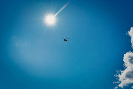 Silhouette of a helicopter against a blue sky with clouds
