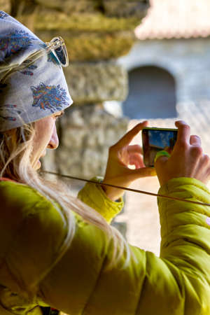 girl photographs the landmark on a mobile phone. Fortress Oreshek
