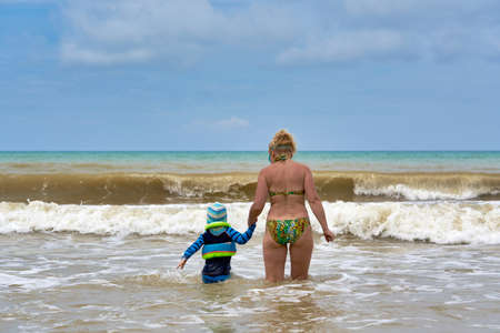 A woman and a child walk into the sea holding hands, view from the back
