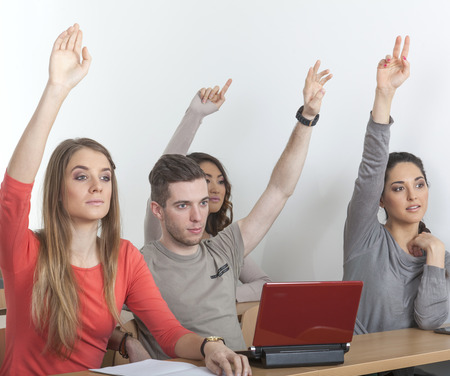 exempted female: Four students in a lecture hall put up their hands