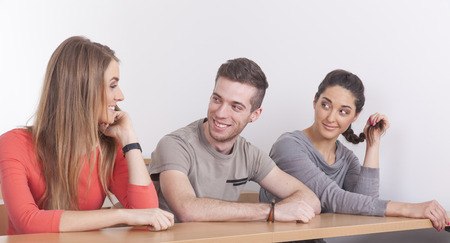 exempted female: Three student sitting in lecture hall looking at each other