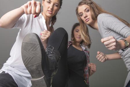 pandilla: Tres polluelos agresivos damas amenazan su víctima Foto de archivo