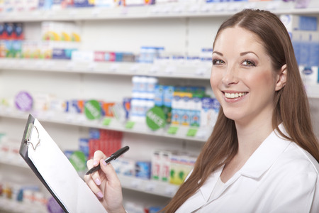 Pharmacist with clipboard while stocktaking in pharmacy Banco de Imagens