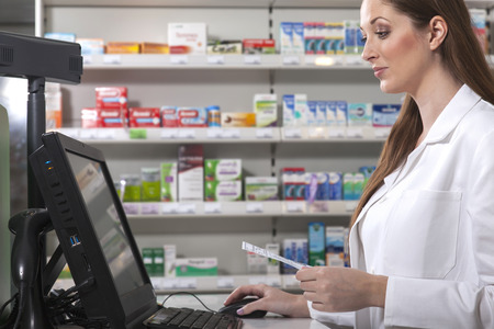 Female pharmacist searches medicine holding a prescription in her hand Banque d'images