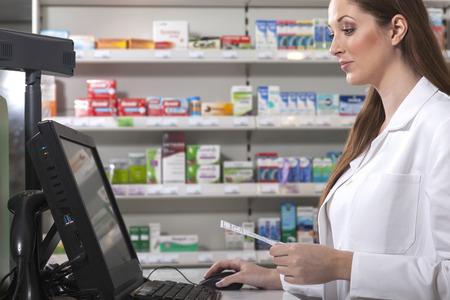 Female pharmacist searches medicine holding a prescription in her hand Stockfoto