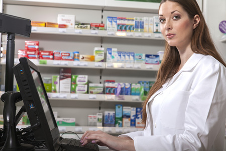 mensch: Female pharmacist searches medicine holding a prescription in her hand Stock Photo