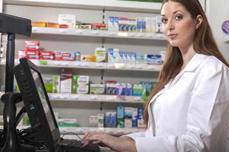 Female pharmacist searches medicine holding a prescription in her hand Standard-Bild