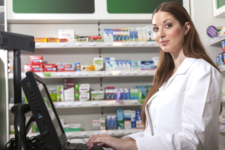 mensch: Female friendly pharmacist at the cash desk computer looks at the camera Stock Photo