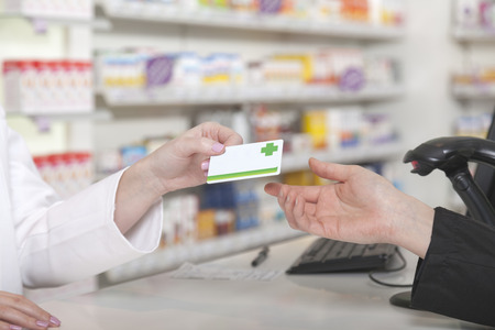 druggist: Customer hands over her payment customer card Stock Photo