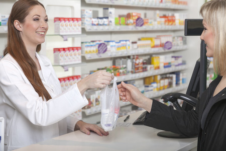 sachet: Friendly female pharmacist hands over a plastic sachet with medicine