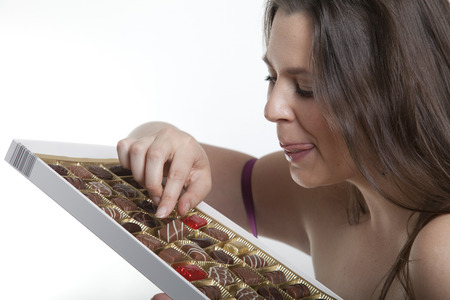 Woman chooses her favorite chocolate truffle from a candy box Stock Photo