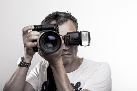 frontal portrait: Frontal portrait of a professional photographer with DSLR camera and speed light on hot show