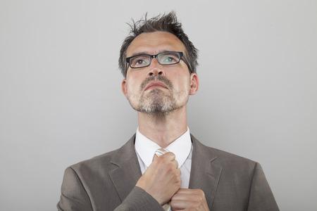 Manager in pinstripe jacket ties his tie looking upwards