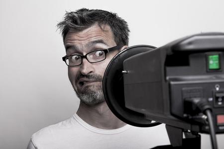 strobe: Photographer sceptically looks into a studio strobe Stock Photo