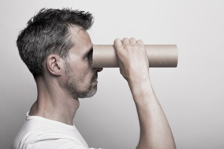 stubbly: Man with a stubbly beard looks through a cardboard tube