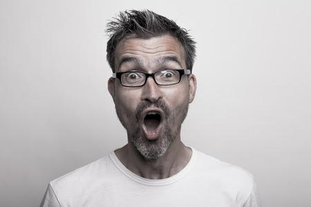 Portret van een enthousiaste man met een bril en stoppelbaard