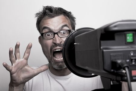 strobist: Photographer sceptically looks into a studio strobe screaming for help