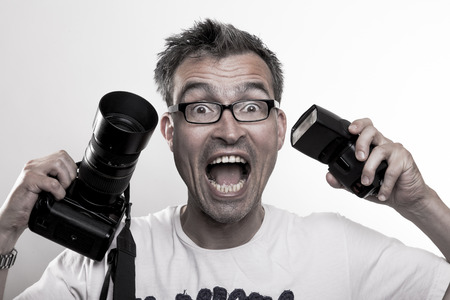 manic: Photographer in white T-Shirt holds a camera and a strobe in his hands while laughing and smiling Stock Photo