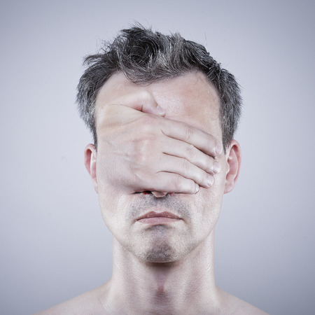 receding hairline: Artistic interpretation of invisibility. Man covers his eyes with his hand.