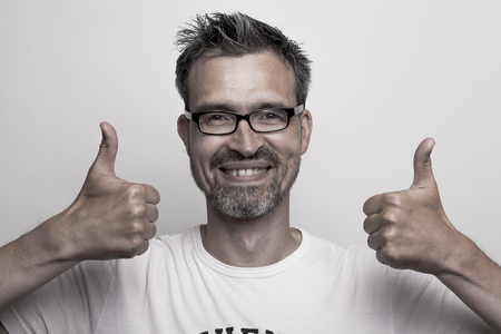 Smart man holds up his thumbs while smiling into the camera Stock Photo