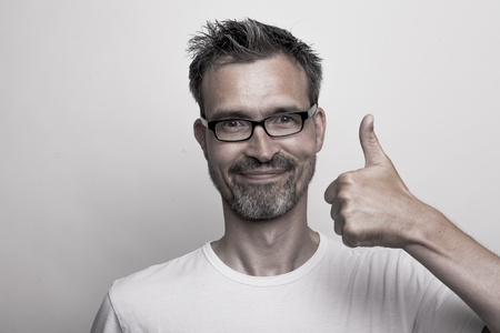 Agreeing man with stubbly beard holds his thumb up Stock Photo