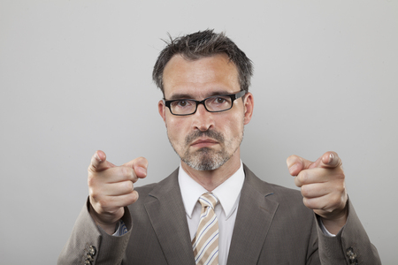 argumentation: Strict teacher trainer points his fingers to the front Stock Photo