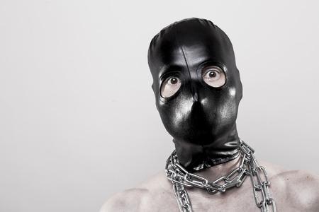 punisher: Mann in schwarzer Ganzkopfmaske und Ketten um den Hals