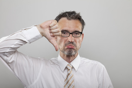 Accountant: Disappointed accountant points out his frustration holding his thumb down and making a negative gesture Stock Photo