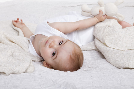 aretes: ni�a ni�o juega en la cama con su mascota peluche Foto de archivo