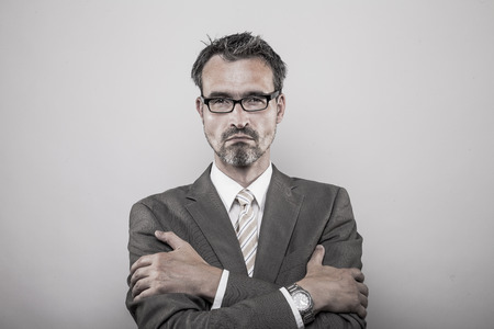 business man in formal jacket shirt and tie holds his arms crossed making a dominant convineced expression Stock Photo