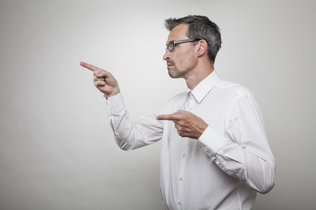 explains: teacher explains something pointing with his index finger to the left, side capture