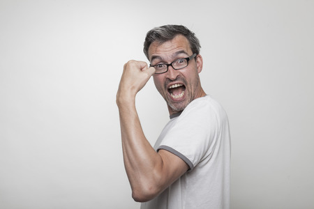 bending: weak man makes a gesture of powerful strength bending over his left arm pumping his biceps muscle Stock Photo