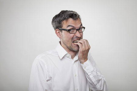 Anxious man in white shirt looking up while chewing his fingers and nails