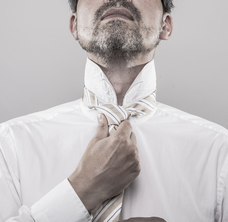 pinstripes: businessman in white shirt and golden tie with blue pinstripes ties his tie in front of the mirror Stock Photo