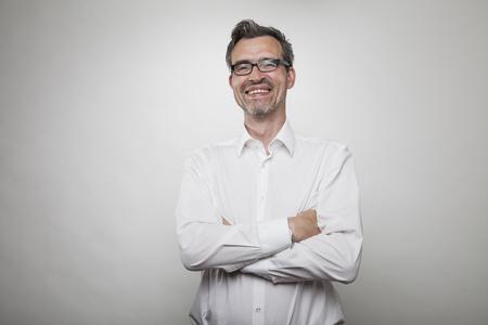 arrogancia: encargado sonriente con el pelo atenuada con una camisa blanca con el cuello desabrochado abierto se encuentra junto a una pared blanca Foto de archivo